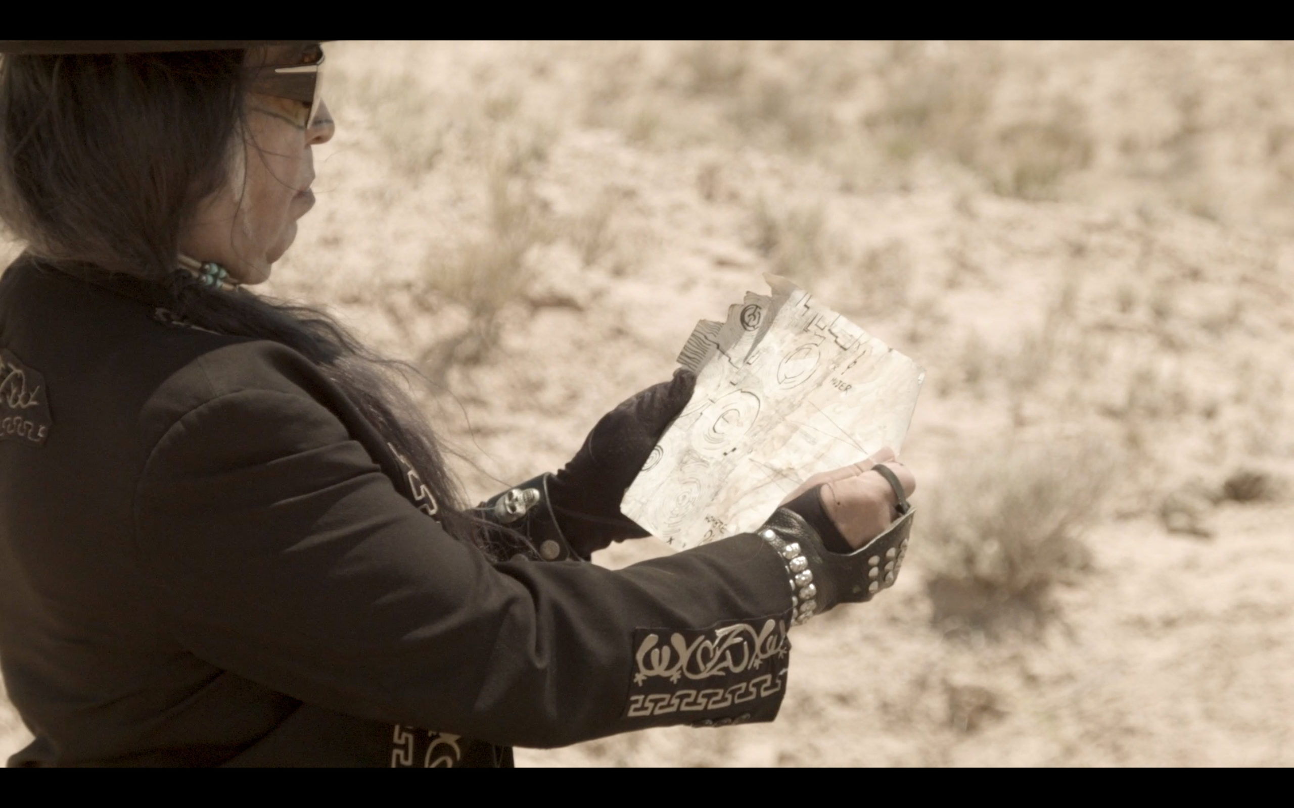 film still of a man holding a piece of paper (a map?) against a desert background